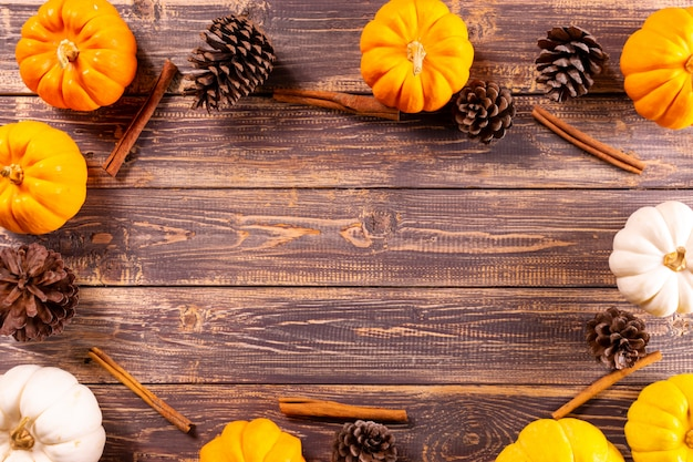Top view of  pumpkins and pine cone on old wooden background.
