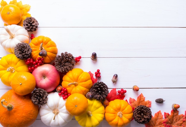 Top view of pumpkins, red berries and pine cones