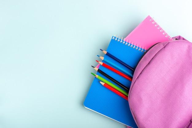 Вид сверху фиолетовая сумка с тетрадями и карандашами на синей поверхности