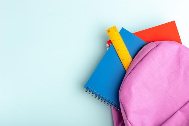 파란색 표면에 카피 북이있는 상위 뷰 보라색 가방