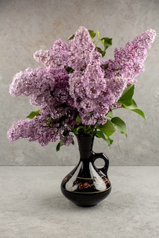 Top view purple flowers beautiful alive inside black jug on the grey background