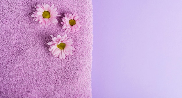 Top view purple flowers and towel with copy-space