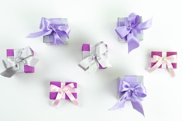 Una vista dall'alto scatole regalo viola con fiocchi su bianco, presente celebrazione di compleanno