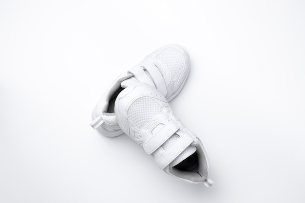 Top view on a pyramid of white child sneakers one sneaker lies on another sneaker isolated on a whit...