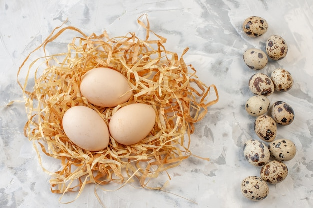 탁자 위의 짚 위에 있는 메추라기 알과 닭고기 달걀