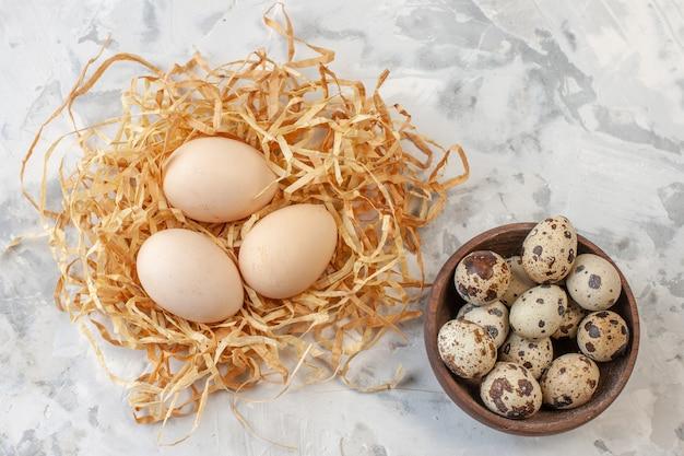 나무 그릇에 있는 메추라기 달걀과 탁자 위에 있는 닭고기 달걀