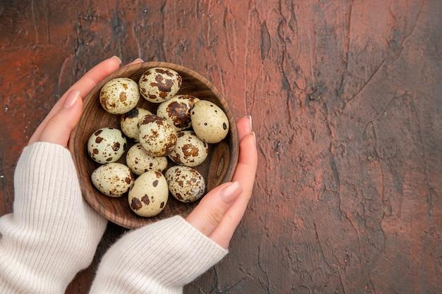 Uova di quaglia vista dall'alto all'interno del piatto sul tavolo scuro