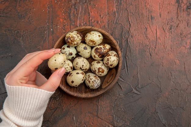暗いテーブルのプレート内のウズラの卵の上面図写真鳥の餌鶏の健康的な生活女性の色