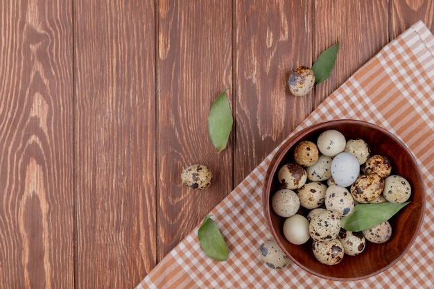 Top view of quail eggs on a wooden bowl on a brown checked tablecloth on a wooden background with copy space