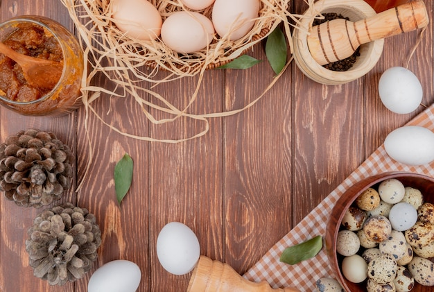 Top view of quail eggs on a wooden bowl on checked cloth with chicken eggs with pine cones on a wooden background with copy space