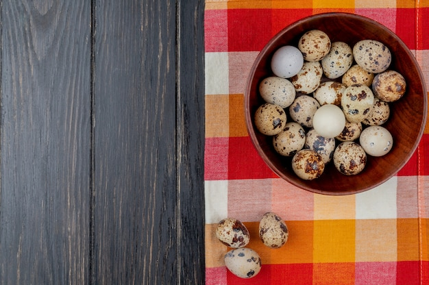Top view of quail eggs on a wooden bowl on checked tablecloth on a wooden background with copy space