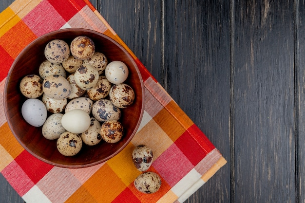 Top view of quail eggs on a wooden bowl on checked tablecloth on wooden background with copy space