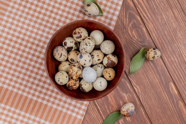 Top view of quail eggs on a wooden bowl on checked tablecloth on a wooden background