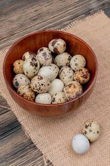 Vista superiore delle uova di quaglie su una ciotola di legno su un panno di sacco su un fondo di legno