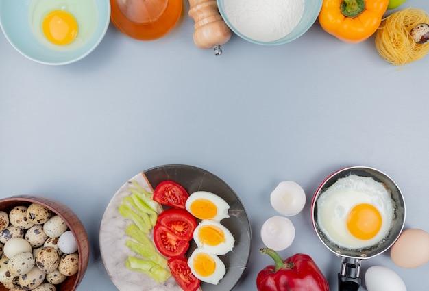 Vista dall'alto di uova di quaglia su una ciotola di legno con uova sode a metà su un piatto con fette di pomodoro con uova fritte su una padella su sfondo bianco con spazio di copia
