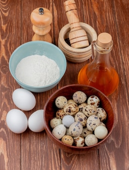 Top view of quail eggs on a wooden bowl with flour on a blue bowl with apple vinegar with white chicken eggs on a wooden background