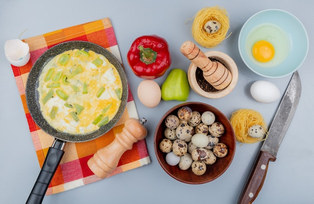Top view of quail eggs on a wooden bowl with fried eggs on a frying pan with bell peppers with knife on white background