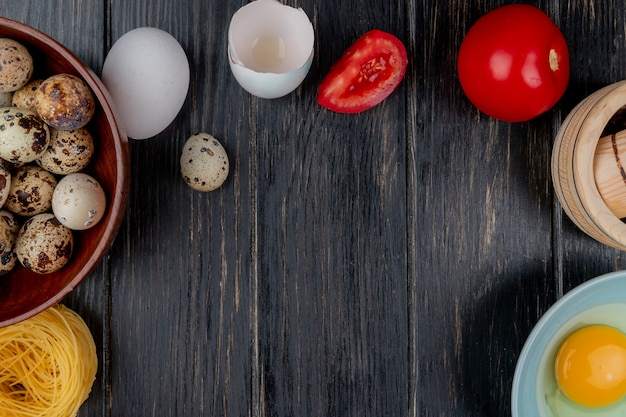 Top view of quail eggs on a wooden bowl with tomato with egg white and yolk on a wooden background with copy space