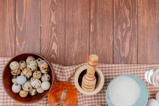 Top view of quail eggs on a wooden bowl with wooden mortar and pestle with flour on a blue bowl on checked tablecloth on a wooden background with copy space