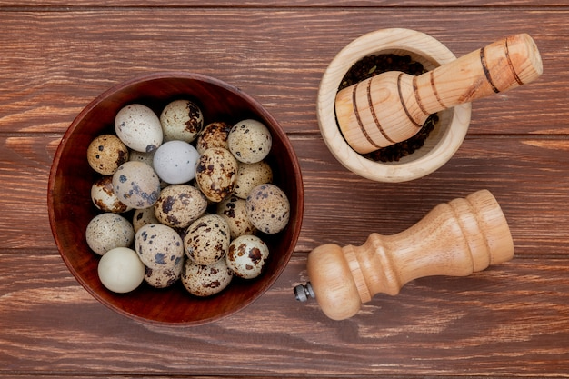 Top view of quail eggs on a wooden bowl with wooden mortar and pestle on a wooden background