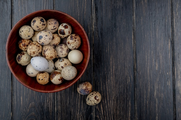 Top view of quail eggs on a wooden bowl on a wooden background with copy space