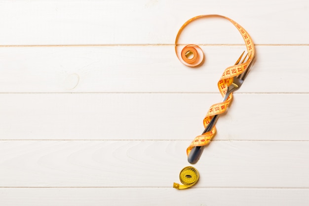 Top view of question mark made of fork and measuring tape on wooden background. diet concept with copy space