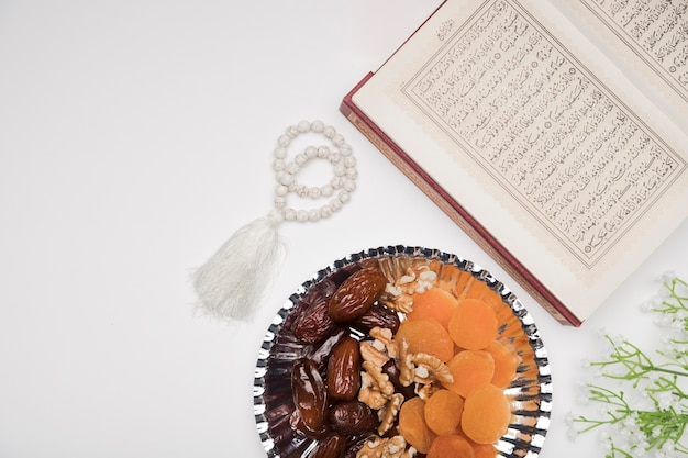 Top view quran and snacks on table