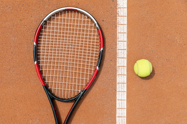 Top view racket and tennis ball on court ground