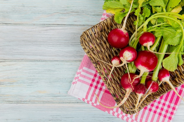 Top view of radishes in basket plate on plaid cloth on right side and wooden background with copy space