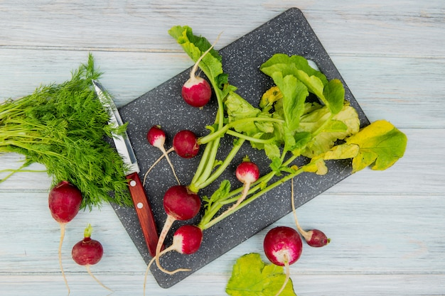 Top view of radishes and knife on cutting board with bunch of dill on wooden background