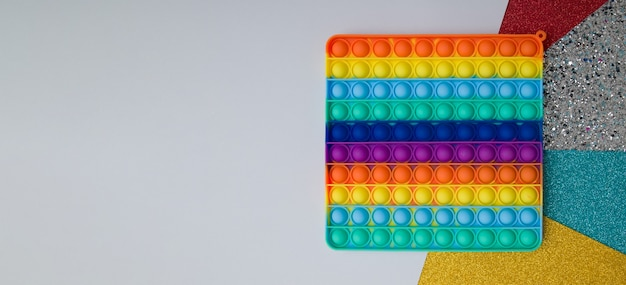 Top view rainbow silicone toy antistress pop it on colorful background. popular children toy sensory push toy banner