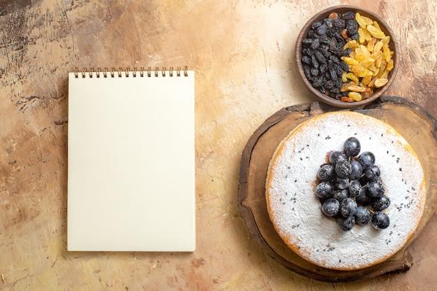 포도 설탕 흰색 노트북 그릇 케이크에 상위 뷰 건포도 녹색과 검은 색 건포도