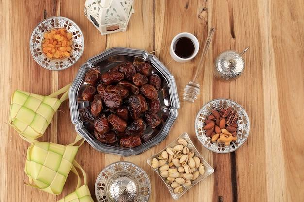 나무 테이블에 복사 공간이 있는 상위 뷰 라마단 음식 및 음료 개념. 날짜 과일, 견과류, 씨앗, 커피, 차, honeyand ketupat. ied al fitr를 위한 아라비아 이슬람식 음식