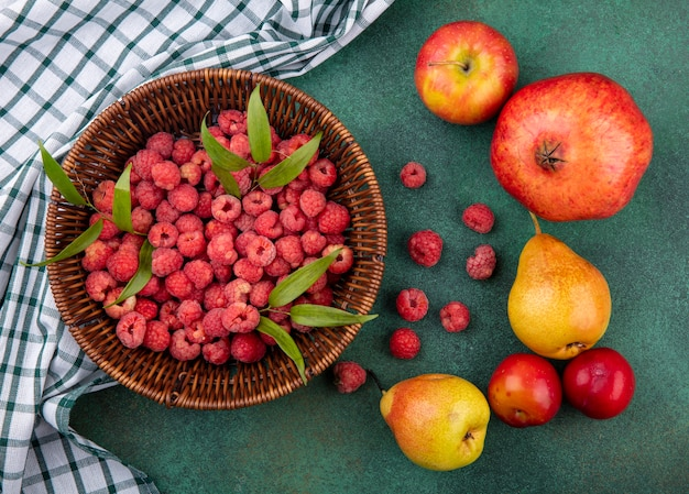 Top view of raspberries in basket on plaid cloth and pattern of pomegranate peach apple plum on green surface