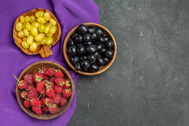 Top view raspberries black and yellow grapes in bowls on purple shawl on dark isolated surface free space