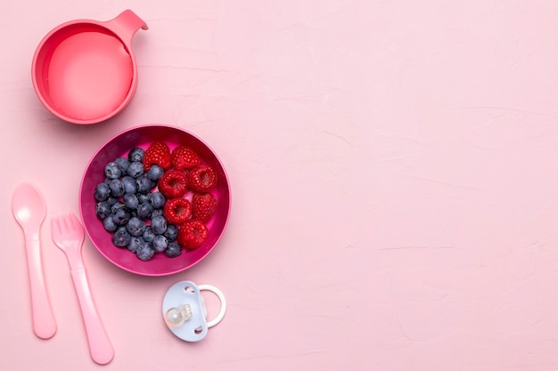 Top view of raspberries and blueberries for baby food with copy space