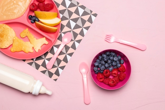 Top view of raspberries and blueberries in bowl with baby bottle and food