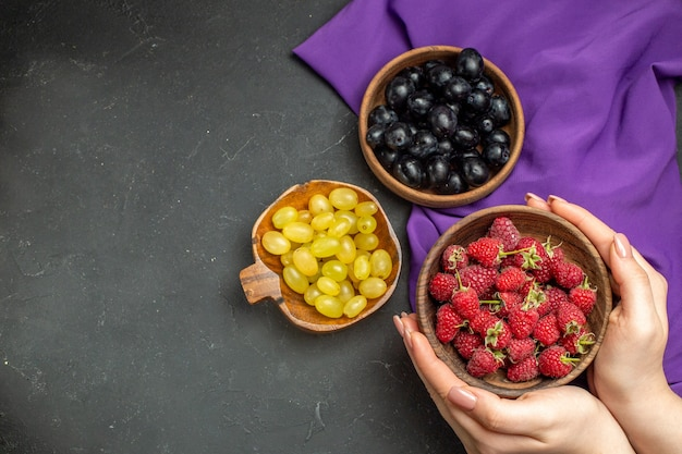 Top view raspberries in bowl in female hands black and yellow grapes in bowls purple shawl dark isolated surface free space
