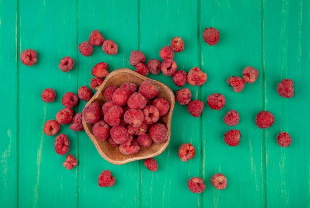 Top view of raspberries in bowl and on green surface