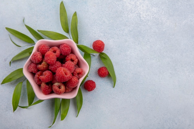 Top view of raspberries in bowl with leaves around on white surface