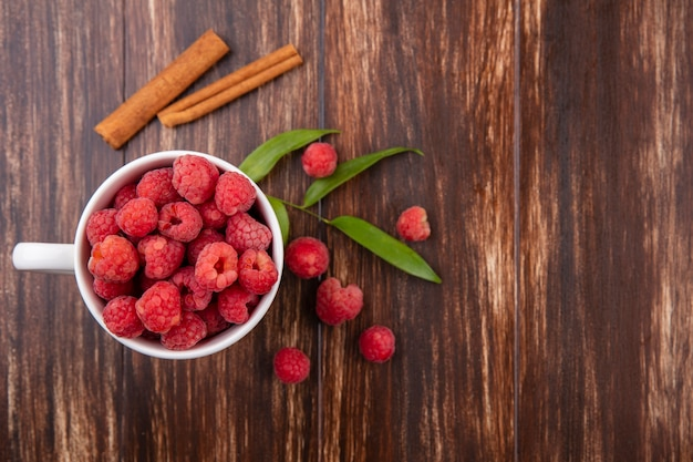 Top view of raspberries in cup with cinnamon and leaves around on wooden surface