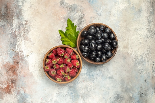 Top view raspberries and grapes in bowls on grey isolated surface with free space
