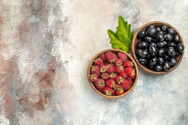 Top view raspberries and grapes in bowls leaves on grey isolated surface with copy space