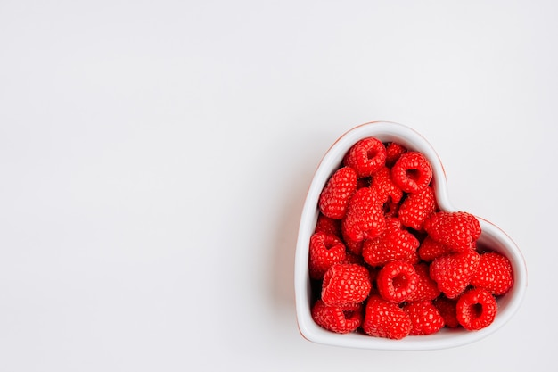 Top view raspberries in heart shaped bowl on white background. horizontal space for text