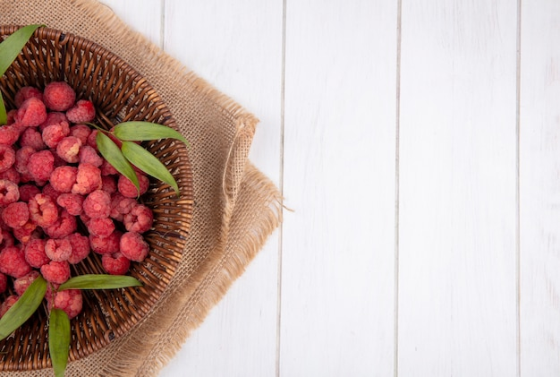 Top view of raspberries and leaves in basket on sackcloth and wooden surface