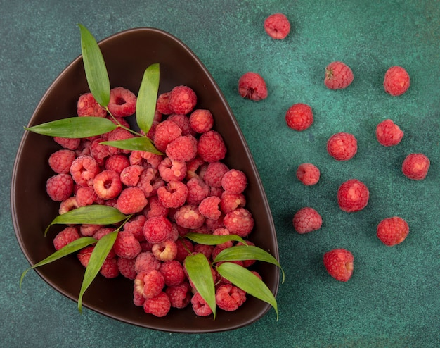 Top view of raspberries and leaves in bowl and pattern of raspberries on green surface