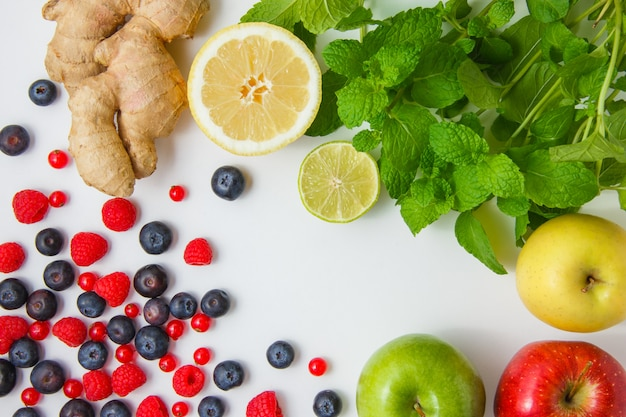 Top view raspberries with apples, blueberries, redcurrants, lemon, ginger, mint leaves on white background. horizontal