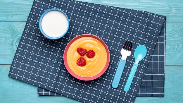 Top view of raspberries with baby food in bowl