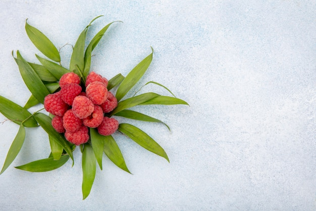 Top view of raspberries with leaves around on white surface