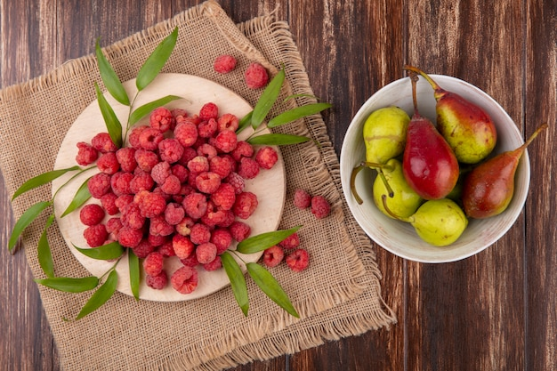 Top view of raspberries with leaves on cutting board on sackcloth and bowl of peach on wooden surface